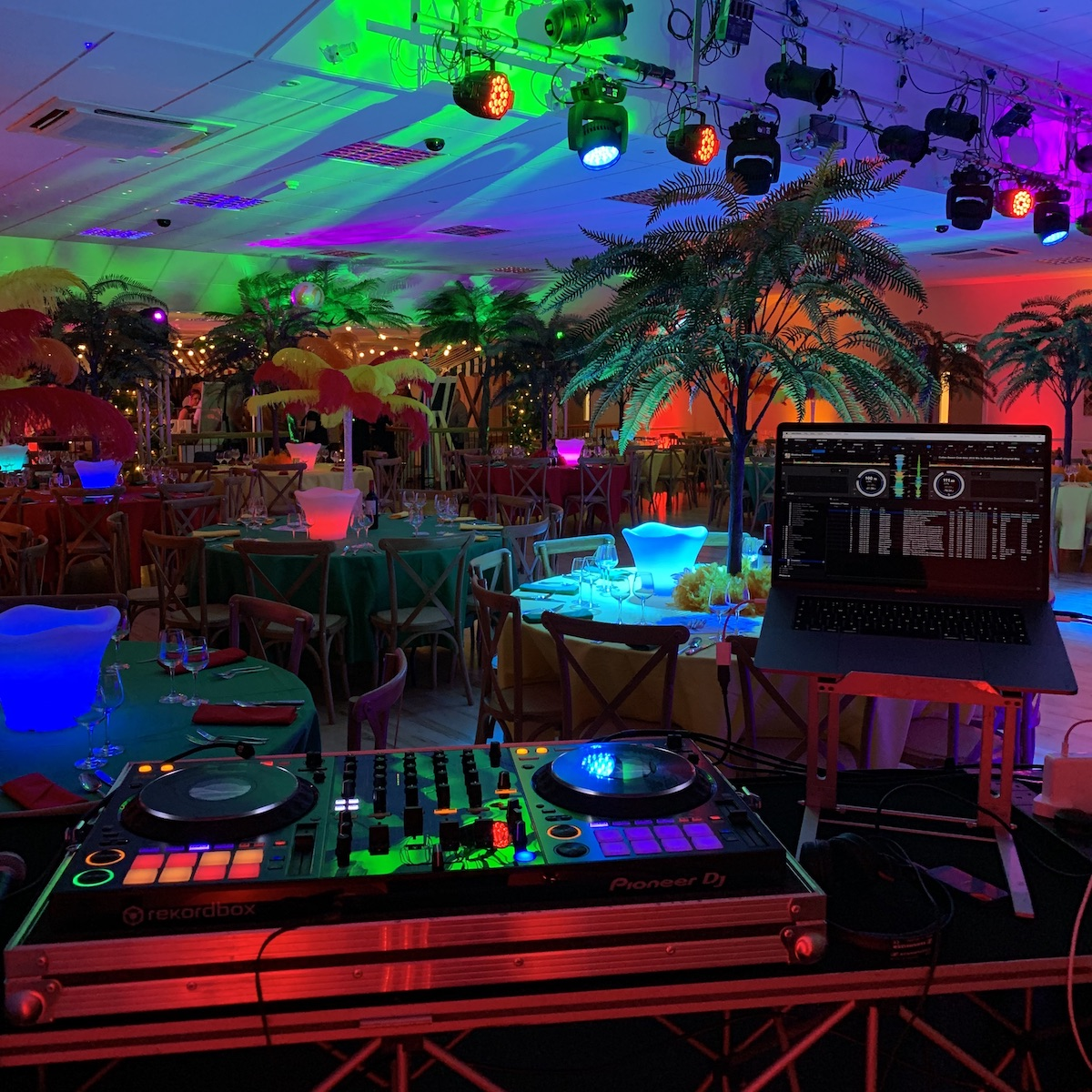 Picture of room decorated for a tropical theme DJ party. Showing palm trees, LED ice buckets, a Pioneer DDJ-1000 DJ controller and a MacBook Pro running RekordBox software.